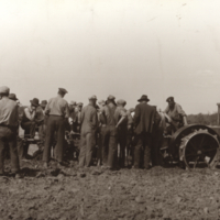 [Men gathered around a tractor and plow at Melfort Research Farm]