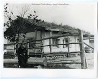 Woman in front of Doukhobor house