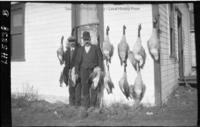 Two men standing by house with geese