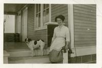 [Woman and dog in front of house]