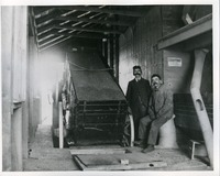 [Two workers posing inside a grain elevator]