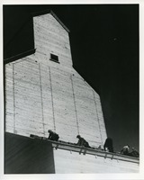 [Workers on the roof of a grain elevator]