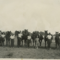 [Young people standing beside their horses]