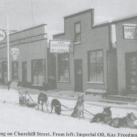 Dog team resting on Churchill Street - from left Imperial Oil, Kay Freedman's Dry Goods, Hansford's Meat and Groceries