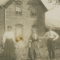 [Three people in front of a house]