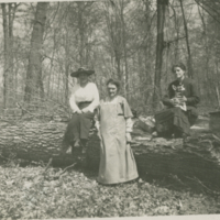 [Three women and a dog on a log]