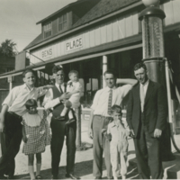 [Four men and three children in front of Ben's Place service station]