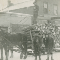 Churchill Street - Loiselle brothers with a load of logs in front of Ed Almond's Insurance office and R Loton's Drug Store