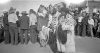 [Three Native men in headdresses standing with a woman]
