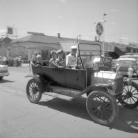 [Man and three children in hats in a car]