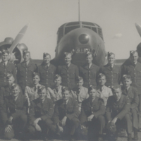 [Group of men standing in front of an aircraft]
