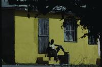 Man seated by yellow house