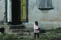 Small child and house with yellow shutter