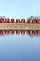 Row of red granaries and reflection