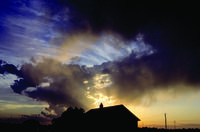 House silhouetted in front of storm clouds