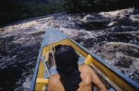 Man in prow of boat, Angel Falls