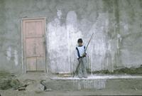 Boy with a long stick in front of a building