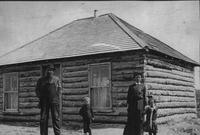 [Family in front of homestead shack]