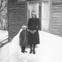 Gertrude and Gene in front of a house