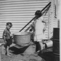 Two children collecting water from the roof