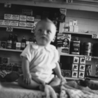 Baby sitting on a table in a grocery store