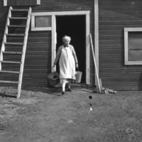 Woman carrying empty pails from her barn