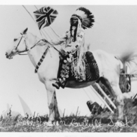 Chief Jimmy Bigstone, carrying a Union Jack flag, mounted on a horse