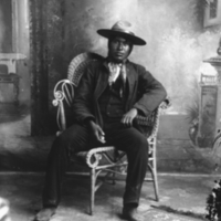 Aboriginal man sitting in a chair with a hat