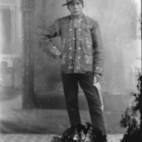 Aboriginal man standing, and wearing a hat