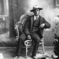 Aboriginal man sitting in a chair with a hat and a watch chain