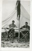 [Two men inside tent]