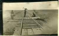[Four men working on the railroad track]