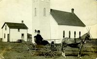 [Man and horse-drawn wagon in front of church]
