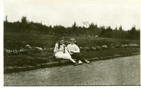 [Two children sitting together in the grass]