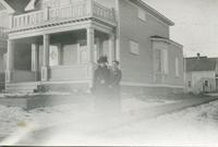 [Women standing in front of a house]