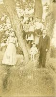 [Image of family posing for a photo by a large tree]