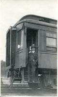 [Man posing in doorway of a rail car]
