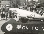 A float bearing a large model fighter aircraft and the words 'On To Victory' participating in the Torch Day Parade