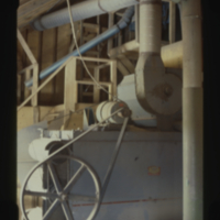 [Belt and chain driven machinery inside grain elevator]