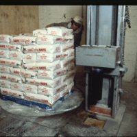 [Man with stack of bags of donut mix inside of a flour mill]