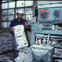 [Man with a bag of donut mix, next to a machine, inside a flour mill]