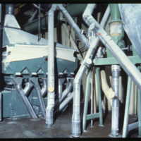 [Machinery and distribution pipes within a flour mill]