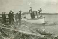 [Men assisting a small steamboat]