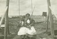 [Two girls on a swing]