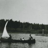 [Four people in a canoe with a sail]