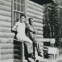 [Two men sitting by a cabin]