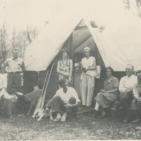 [Group of people in front of shack tent]