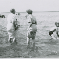 [Women in dresses wading in lake]
