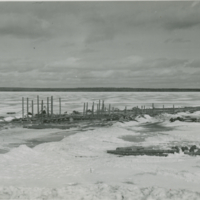 [Log structure built on froze lake - likely for cutting ice]